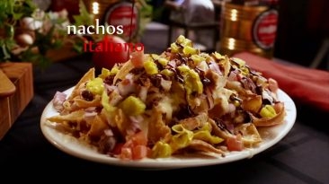 "A plate of loaded nachos with text reading, ""nachos italiano"""
