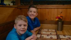 Two young boys smiling at the as they sit at a table looking over a menu