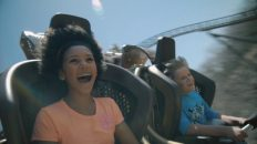 A young girl and boy laughing while riding a roller coaster